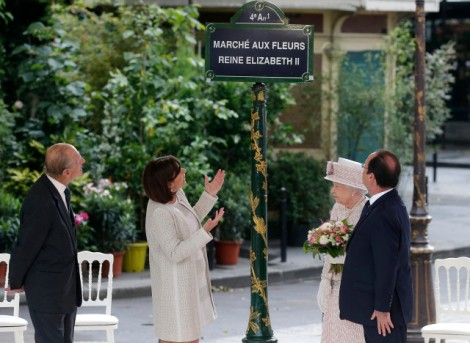 Britain's Queen Elizabeth, Prince Philip, French President Hollande and Paris Mayor Hidalgo unveil a plaque during a visit at the flower market in Paris